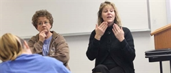 Photo of a person speaking in sign language to a group